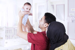 Parents lifting up their baby in bedroom Stock Photography