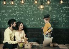 Parents listening their son, chalkboard on background. Homeschooling concept. Parents teaching kid at home. Boy. Presenting his knowledge to mom and dad. Smart stock photo