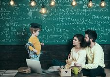 Parents listening their son, chalkboard on background. Homeschooling concept. Parents teaching kid at home. Boy Stock Photo