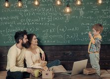 Parents listening their son, classroom, laptop, chalkboard on background. Homeschooling concept. Parents teaching kid at. Home. Boy presenting his knowledge to royalty free stock images