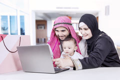Parents and little boy looking at laptop Stock Photos