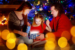 Parents and little daughter opening a magical Christmas gift. Young parents and their little daughter opening a magical Christmas gift by a Christmas tree in Royalty Free Stock Photos