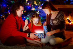 Parents and little daughter opening a magical Christmas gift. Young parents and their little daughter opening a magical Christmas gift by a Christmas tree in Royalty Free Stock Photo
