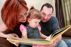Parents and little daughter reads book Royalty Free Stock Photo