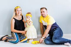 Parents with a little daughter are sitting on the floor and eating a cake royalty free stock image