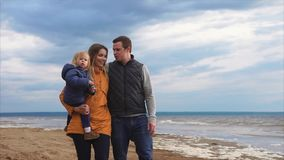 Parents with little daughter walking by the sea on cold day stock footage