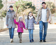 Parents and little daughters taking a walk in park Royalty Free Stock Photo