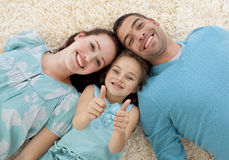 Parents and little girl on floor with thumbs up Royalty Free Stock Photo