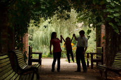 Parents and little girl in garden in plant tunnel Stock Image