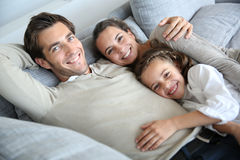 Parents with little girl lying on sofa feeling hapy Royalty Free Stock Images