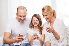 Parents and little girl with smartphones at home Royalty Free Stock Photo