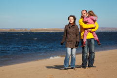 Parents with little girl walk on autumn beach stock image