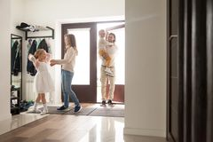 Couple with children in hallway gather for a walk. Parents and little preschool children standing in hallway opposite front door at home. Mother helps girl stock image