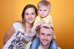 Parents with little son on father's shoulders. Family portrait of young parents with little son on father's shoulders Royalty Free Stock Photos