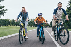 Parents and little son riding bicycles together in park Royalty Free Stock Photography