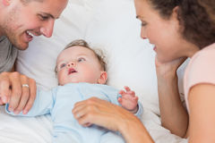 Parents looking at baby boy in bed Stock Photography