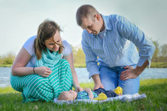 Parents looking at baby. Parents lean over a baby laying on the ground on a blanket Royalty Free Stock Images