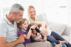 Parents looking at children playing video game. Happy parents looking at children playing video game while sitting on sofa at home Royalty Free Stock Images
