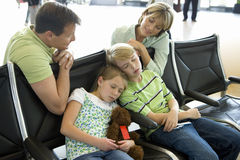 Parents looking at children sleeping on seats in airport departure lounge, girl (7-9) holding soft toy royalty free stock images