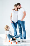 Parents looking at cute little daughter sitting on skateboard Stock Photo