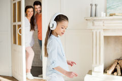 Parents looking at cute little girl in white headphones royalty free stock images