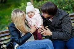 Parents looking at daughter sitting on bench in park Stock Photos