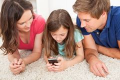 Parents looking at daughter using smart phone Stock Photography
