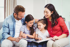 Parents looking in picture book while sitting with daughters Stock Photos