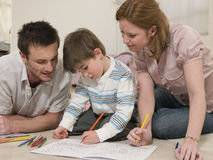 Parents Looking At Son Coloring In Drawing Book. Young parents looking at son coloring in drawing book on floor Stock Photos