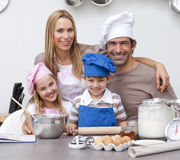 Parents a los niños de ayuda que cuecen al horno en la cocina fotografía de archivo libre de regalías