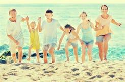 Parents a los niños que corren en la playa Imagen de archivo