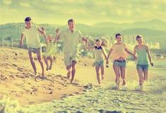 Parents a los niños que corren en la playa Fotografía de archivo libre de regalías