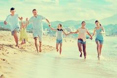 Parents a los niños que corren en la playa Imagenes de archivo