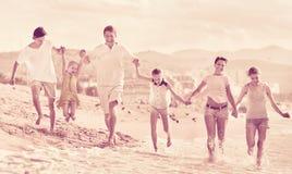 Parents a los niños que corren en la playa Fotos de archivo