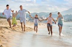 Parents a los niños que corren en la playa Fotografía de archivo