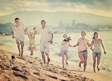 Parents a los niños que corren en la playa Fotos de archivo libres de regalías