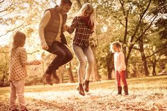 Parents love children`s games. Parents jumping across jump rope and little girl holding rope royalty free stock photos