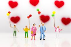 Parents love each other happily, with children playing balloons are behind, used as a wedding anniversary concept.  Stock Images