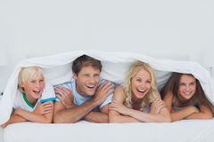 Parents lying on bed with their children. Under the blanket Stock Photography