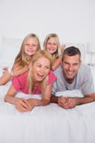 Parents lying in bed with their twins Royalty Free Stock Photo