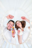 Parents making funny faces looking at baby in crib Stock Photos