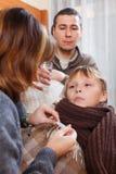 Parents measuring  temperature of   son. Parents measuring the temperature of  unwell son Royalty Free Stock Photography