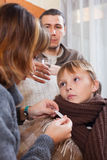 Parents measuring the temperature of the son. Parents measuring the temperature of the unwell son stock image