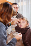 Parents measuring the temperature of  unwell boy Royalty Free Stock Images