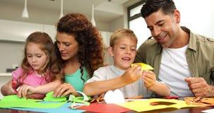 Parents mignons et enfants faisant des arts et des métiers à la table de cuisine banque de vidéos