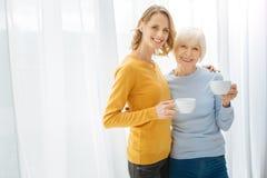 Parents mignons positifs étreignant et souriant tout en buvant de leur thé Photographie stock