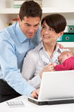 Parents With Newborn Baby Working From Home Stock Image