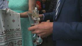 Parents of newlyweds holding loaf and glasses. Russian wedding tradition - father and mother of newlyweds meet them with loaf and with glasses during the wedding stock video footage