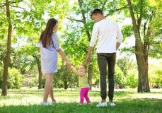 Parents o apoio de sua filha do bebê quando ela que aprende imagens de stock