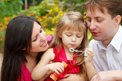 Parents observe as daughter blows soap bubble Royalty Free Stock Image